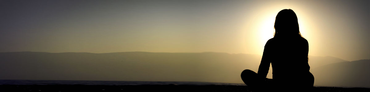 Silhouette of a woman against sunrise and mountains